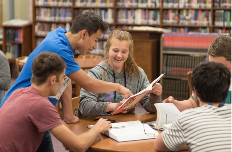 A group of students in a library reviewing a textbook together.