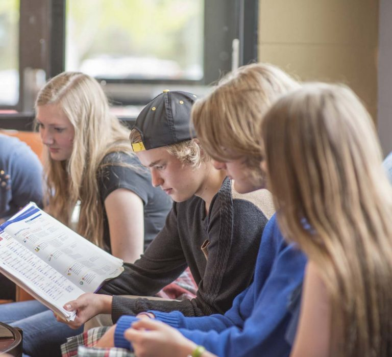 A group of students reviewing a textbook in a university common area.
