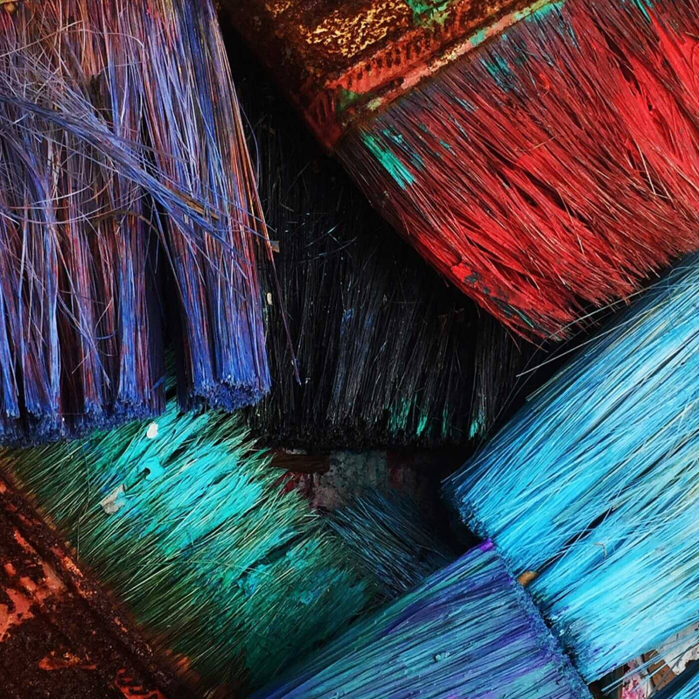 A closeup of paintbrushes with various colors of paint on them.