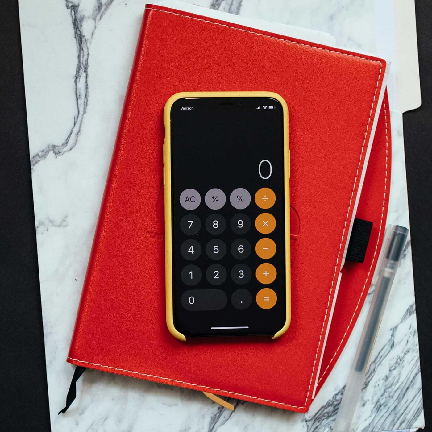 A smartphone with a calculator app open sitting on top of a notebook.