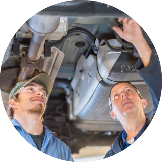 Two men working on the underside of a car.