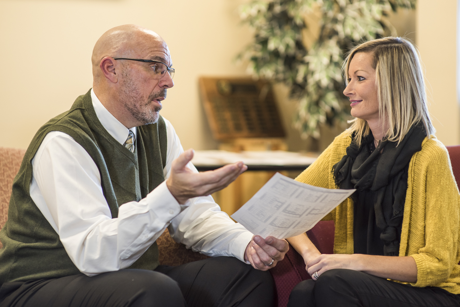 A man and woman chatting and reviewing a document.