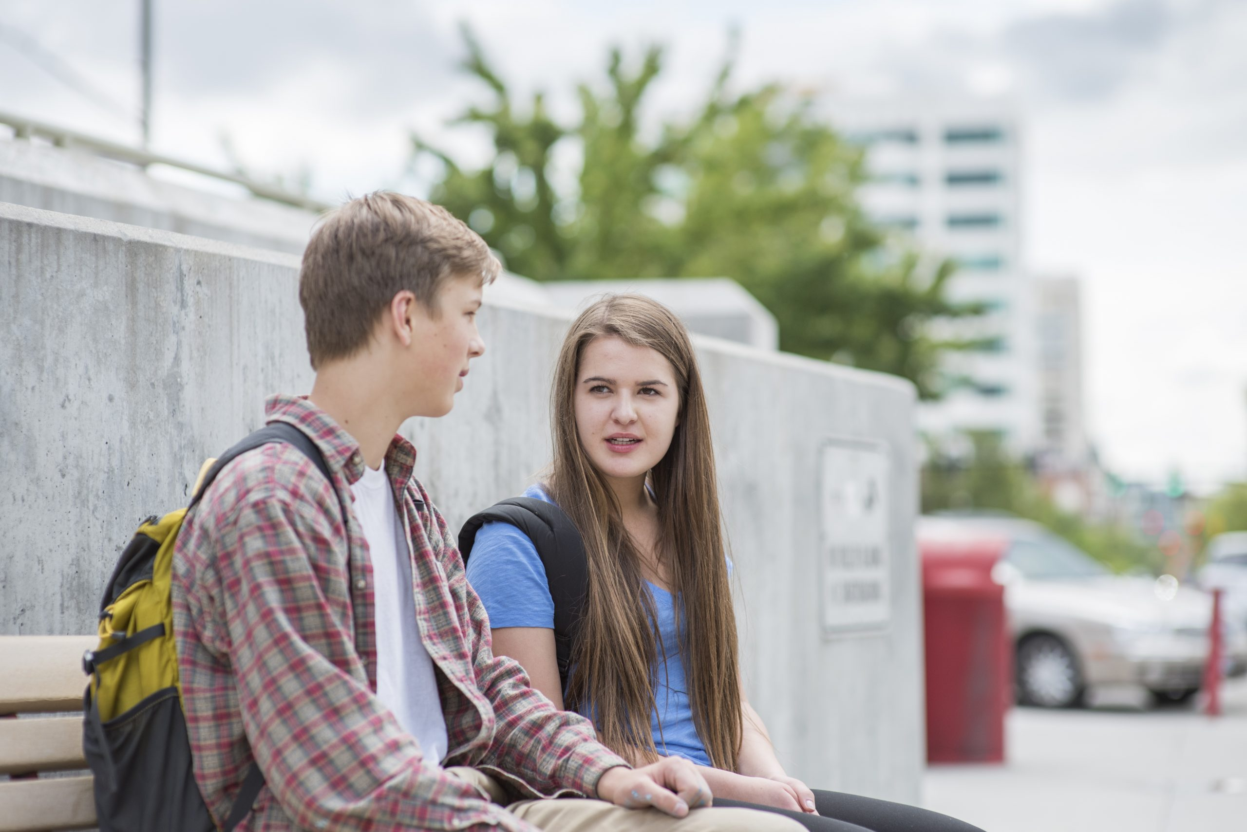 Two students sitting on a bench outside on campus talking.