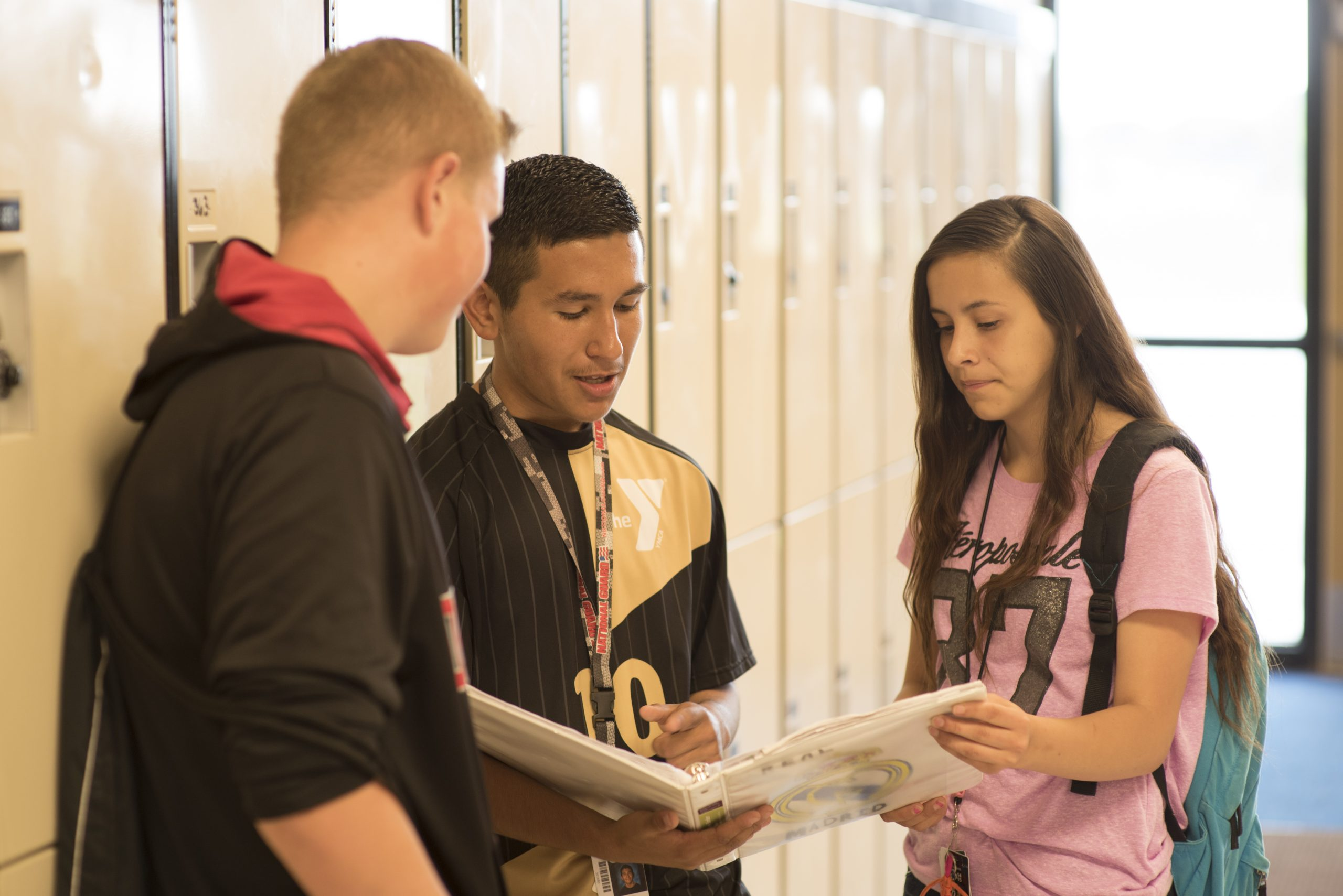Three students reviewing contents of a binder in a school standing by lockers.