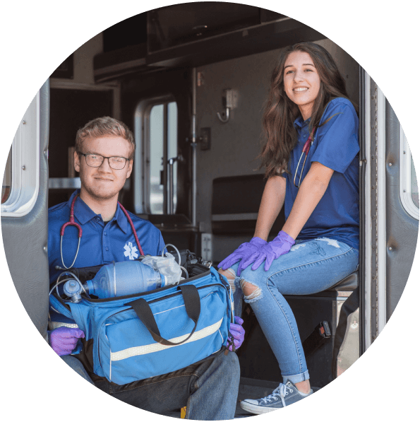 Two students sitting in the back of an ambulance during a medical training exercise.