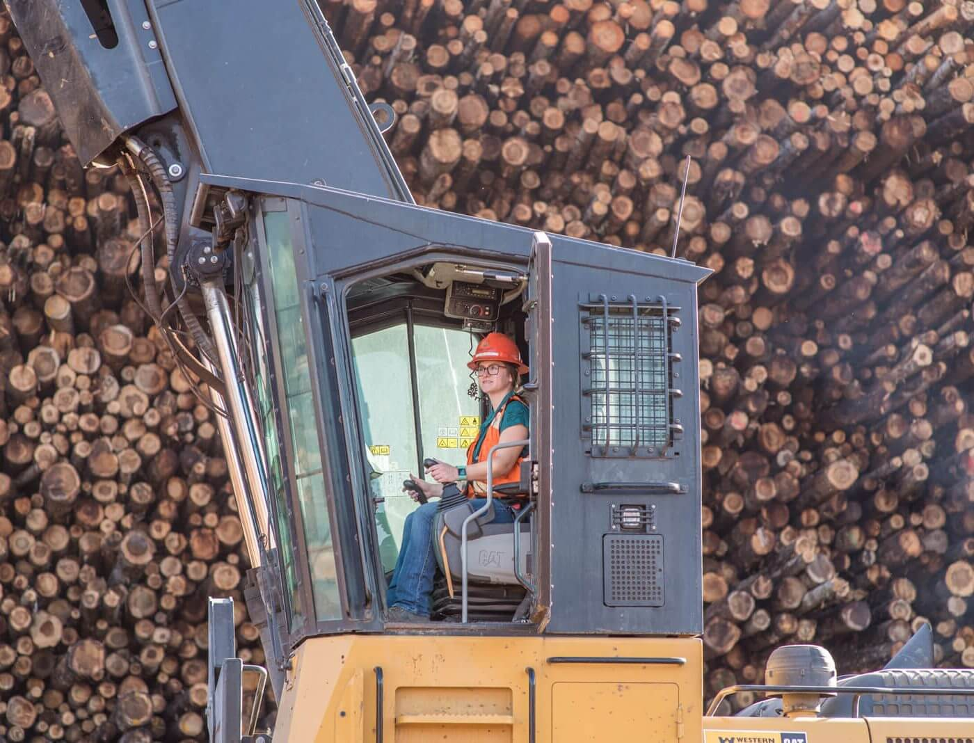 A woman operating large machinery in front of a large pile of logs.
