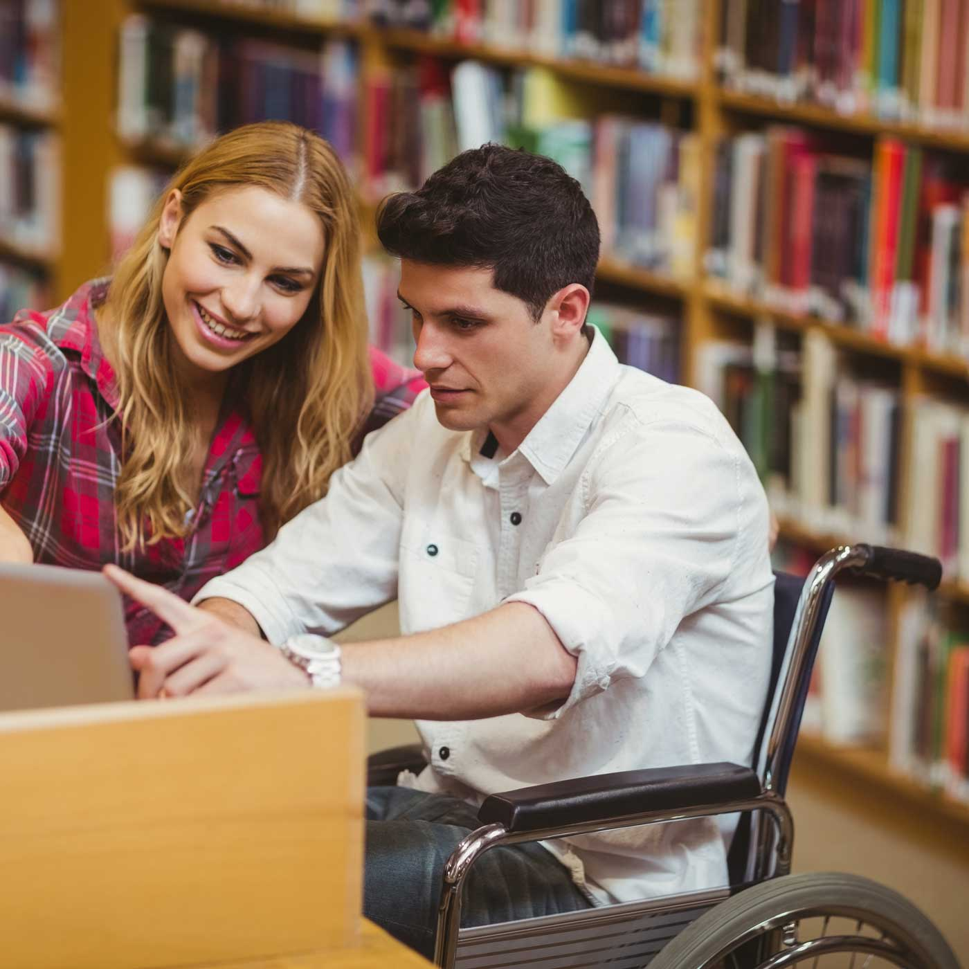 Two students studying together in a library.