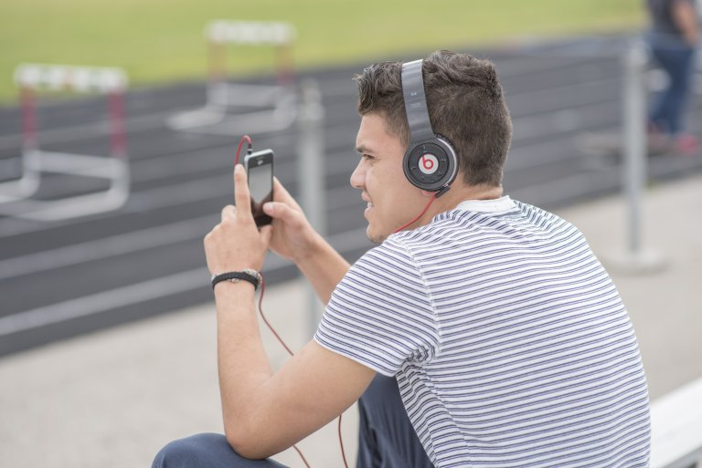 Student sitting beside a track looking at his phone and wearing headphones