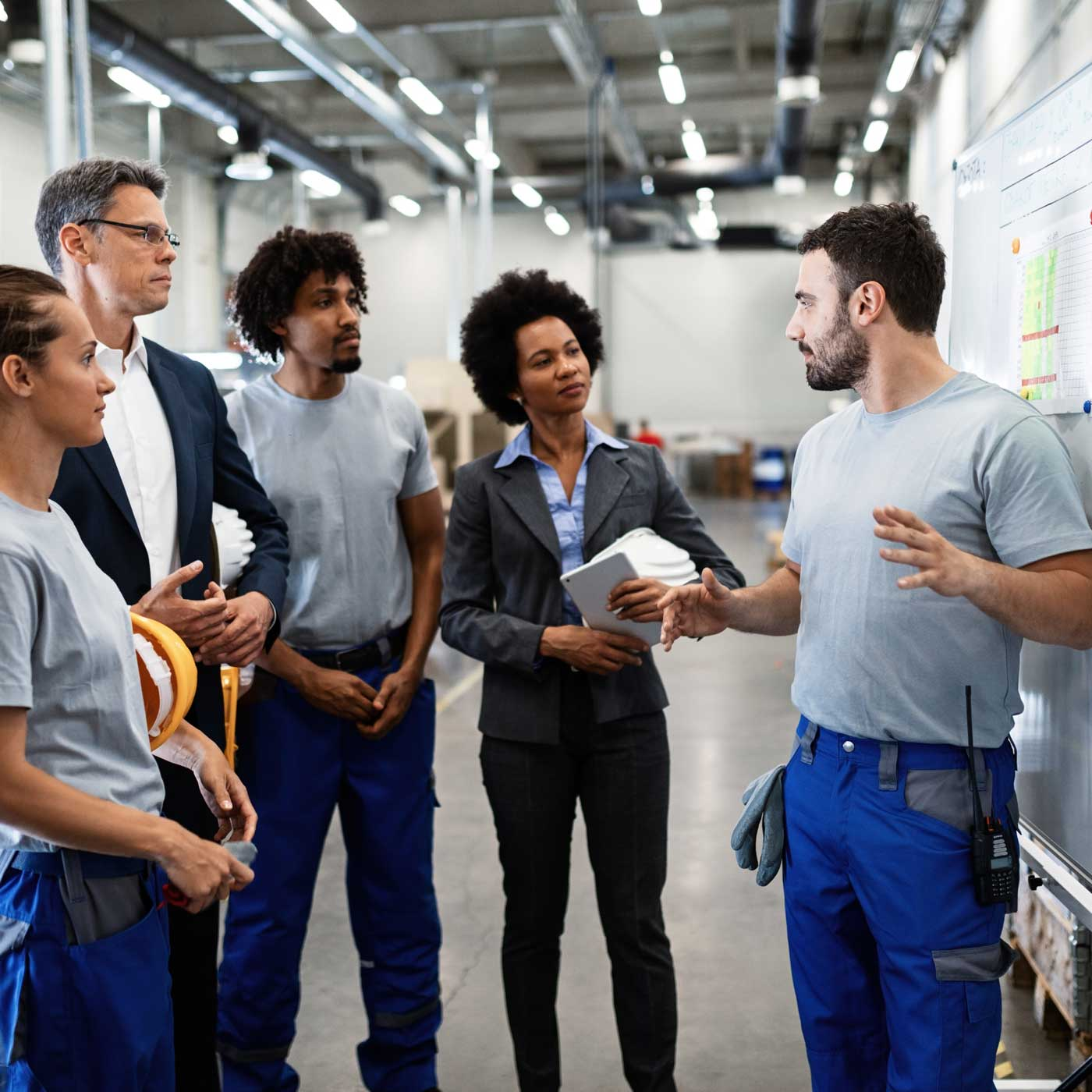 A group of workers in a warehouse having a standing meeting.