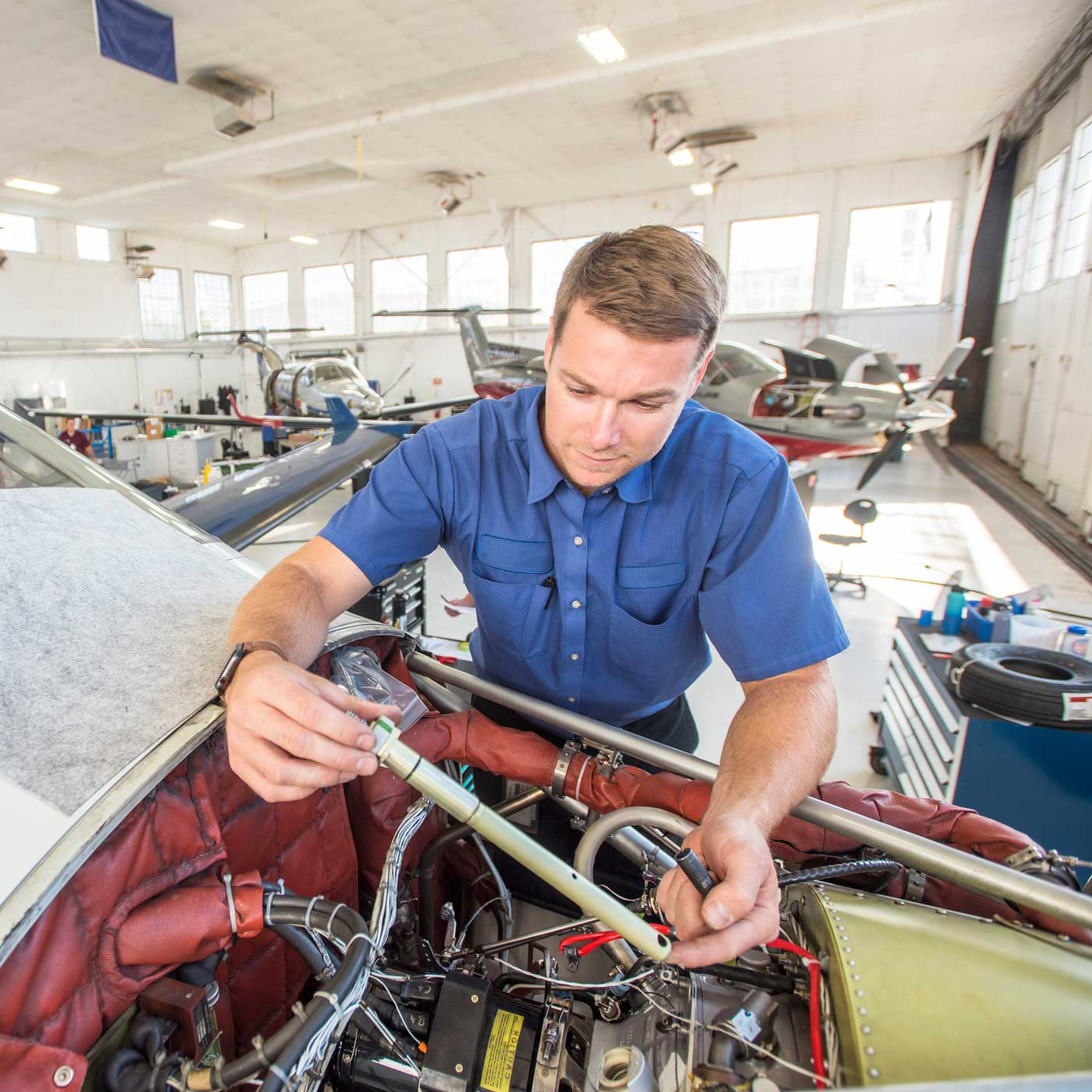 A man working on the engine of an airplane.